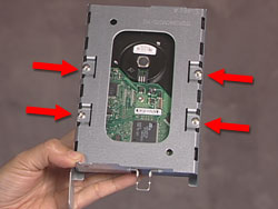Four screws that secure the hard drive