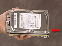 Hard drive with an arrow showing the location of the connectors (at the open end of the cage)