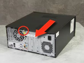 Image of a computer on its side with a side panel retaining screw called out and a directional arrow pointing to the rear of the computer.