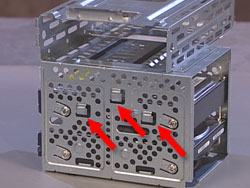 Three tabs on the side of the hard drive cage