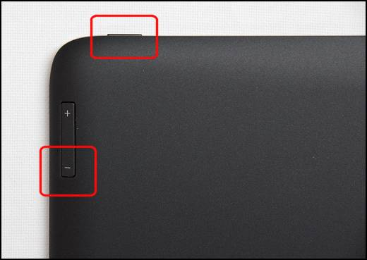 Photograph showing the location of the power and volume buttons. As facing the back of the tablet, the Power button is located in the upper left top edge and the Volume Down  button being the lower portion of a toggle switch in the upper left edge on the back.